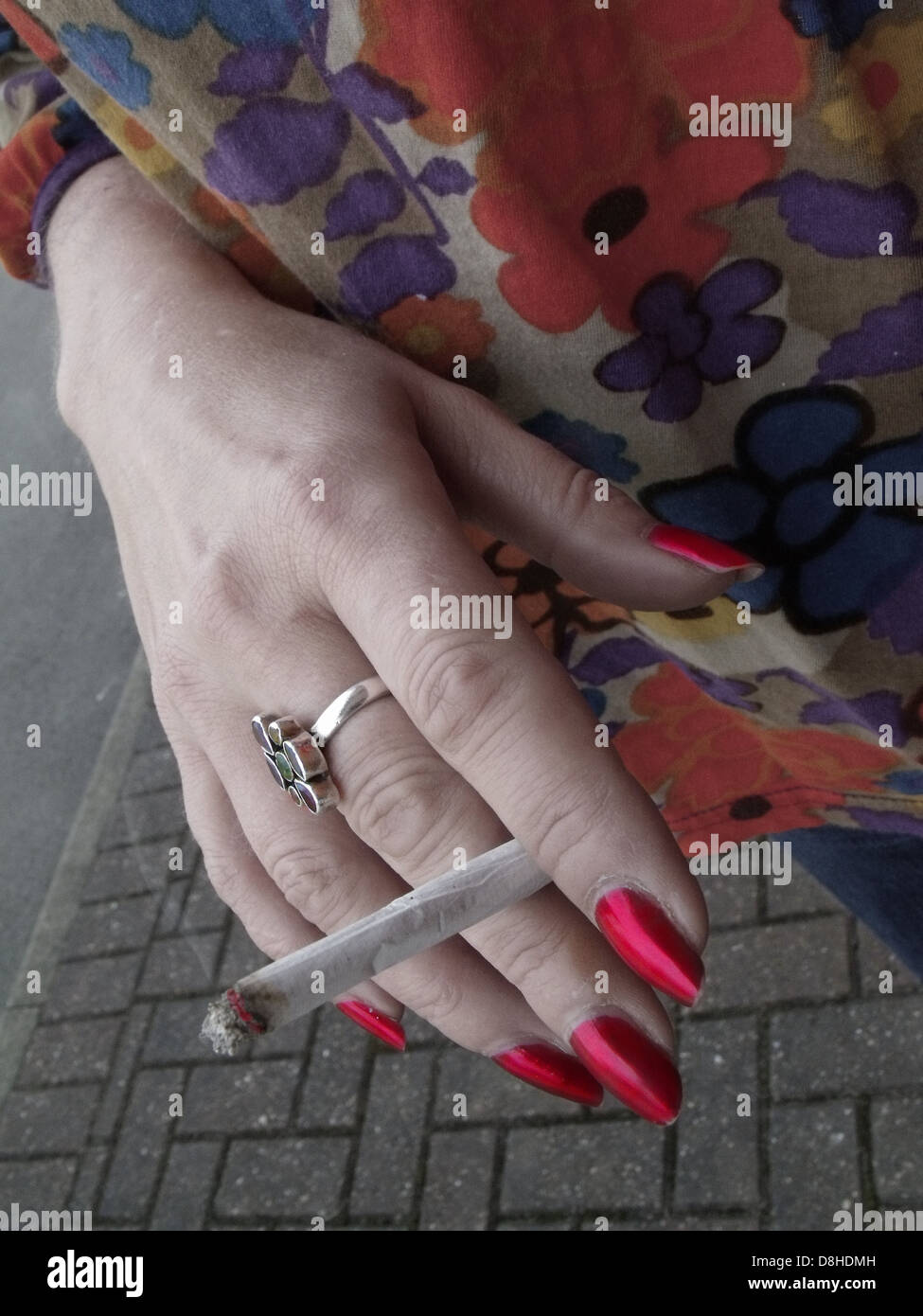 Lady smoker holding a home-made roll up, smoking outside a building in England ,UK where a smoking ban in public - Stock Image