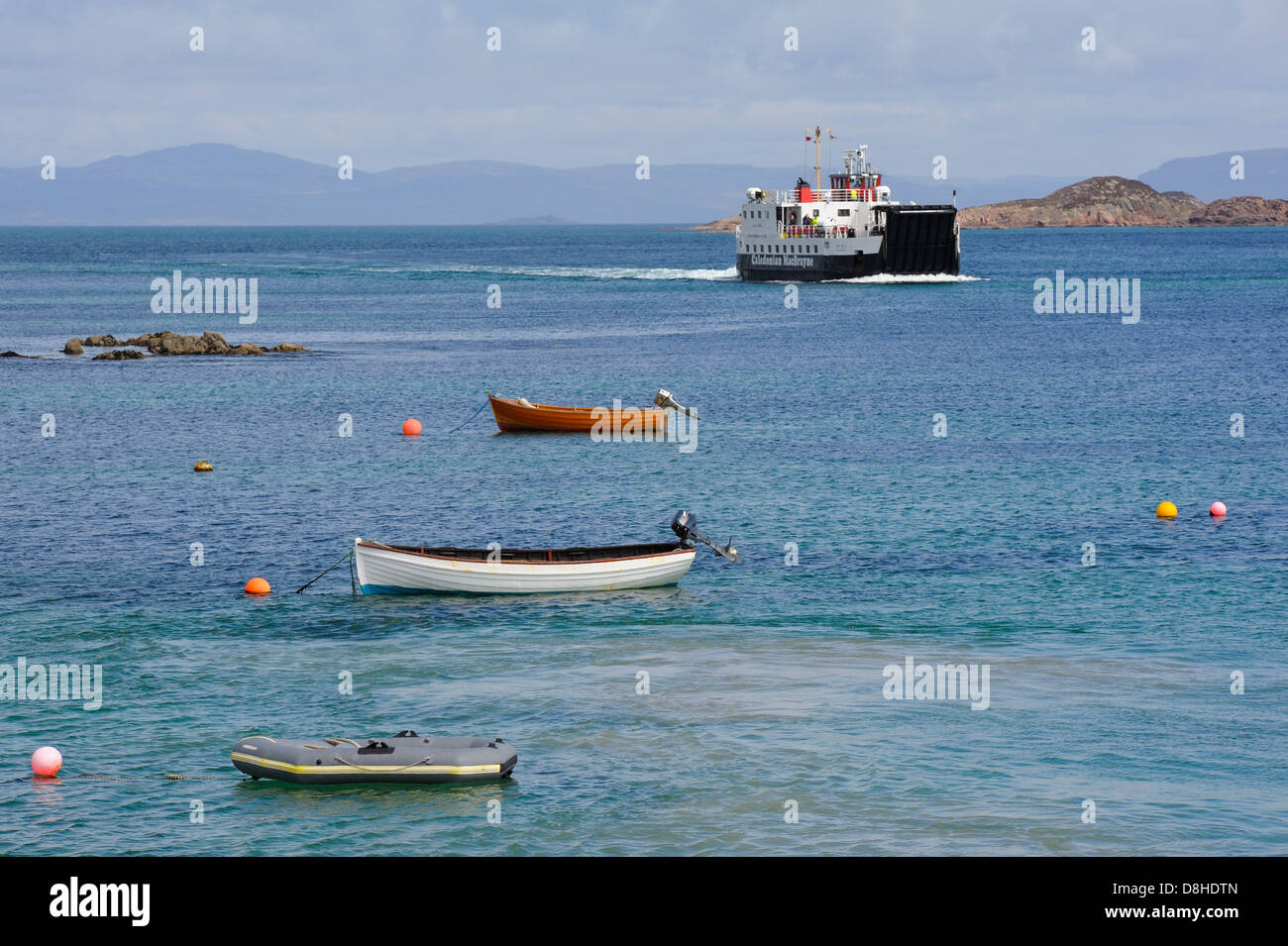 View across the sound of iona showing the calmac ferry bringing tourists and islanders across to the isle of iona - Stock Image