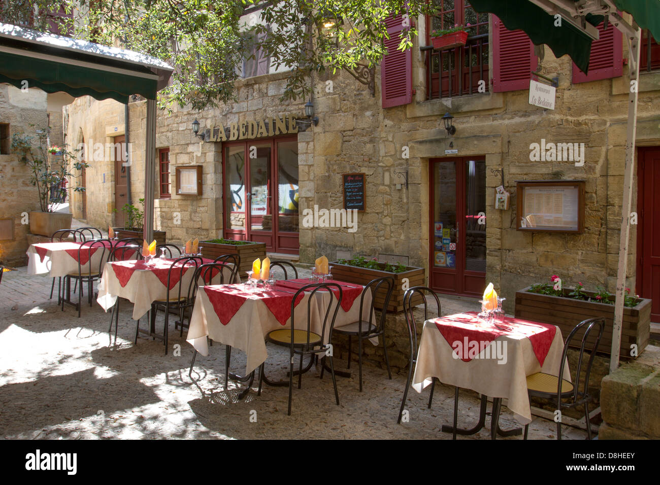 Sun-dappled outdoor courtyard restaurant among medieval sandstone buildings in charming Sarlat, Dordogne region - Stock Image