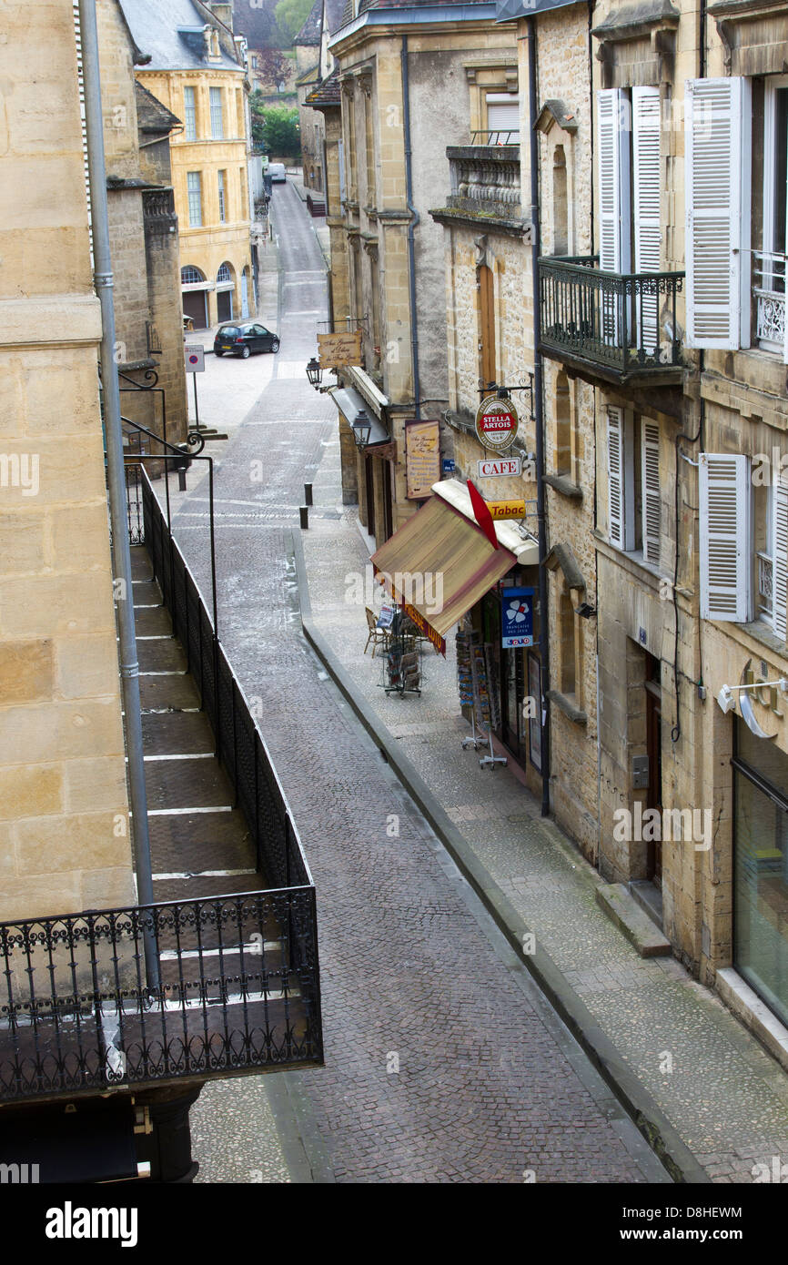 Sandstone buildings, shops and balconies along cobblestone street of Rue Victor Hugo, early morning in Sarlat, France - Stock Image