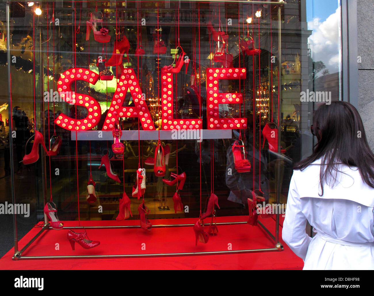 Woman in white mac looking at a red SALE sign in a shoe shop window London GB - Stock Image