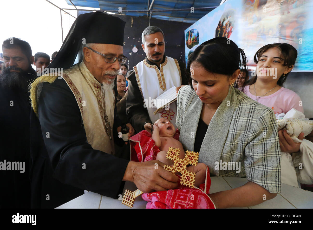 baptism of a baby by catholic coptic bishop KYRILLOS WILLIAM of Asyut diocese, Egypt - Stock Image