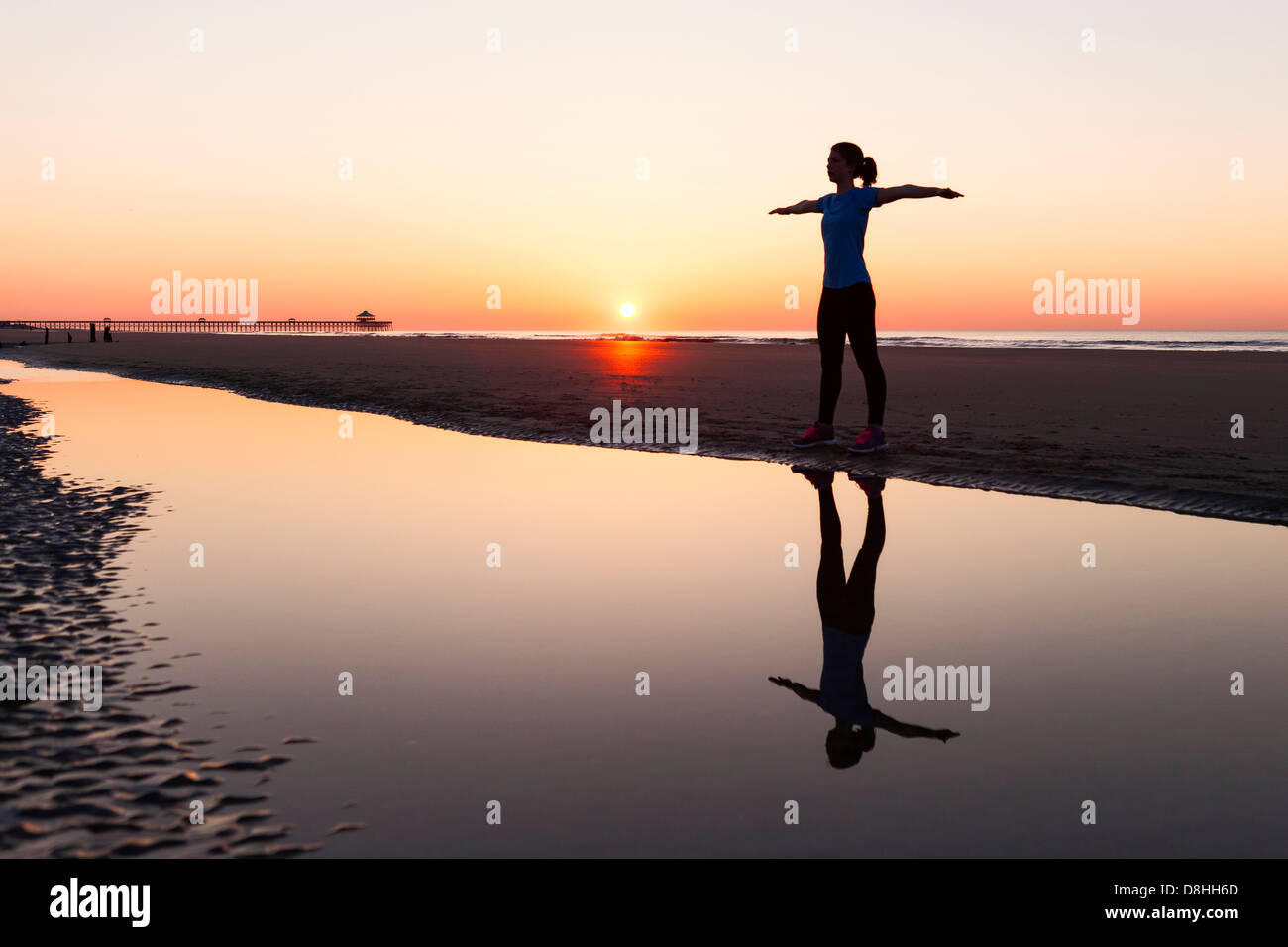 Athlete stretching near ocean - Stock Image