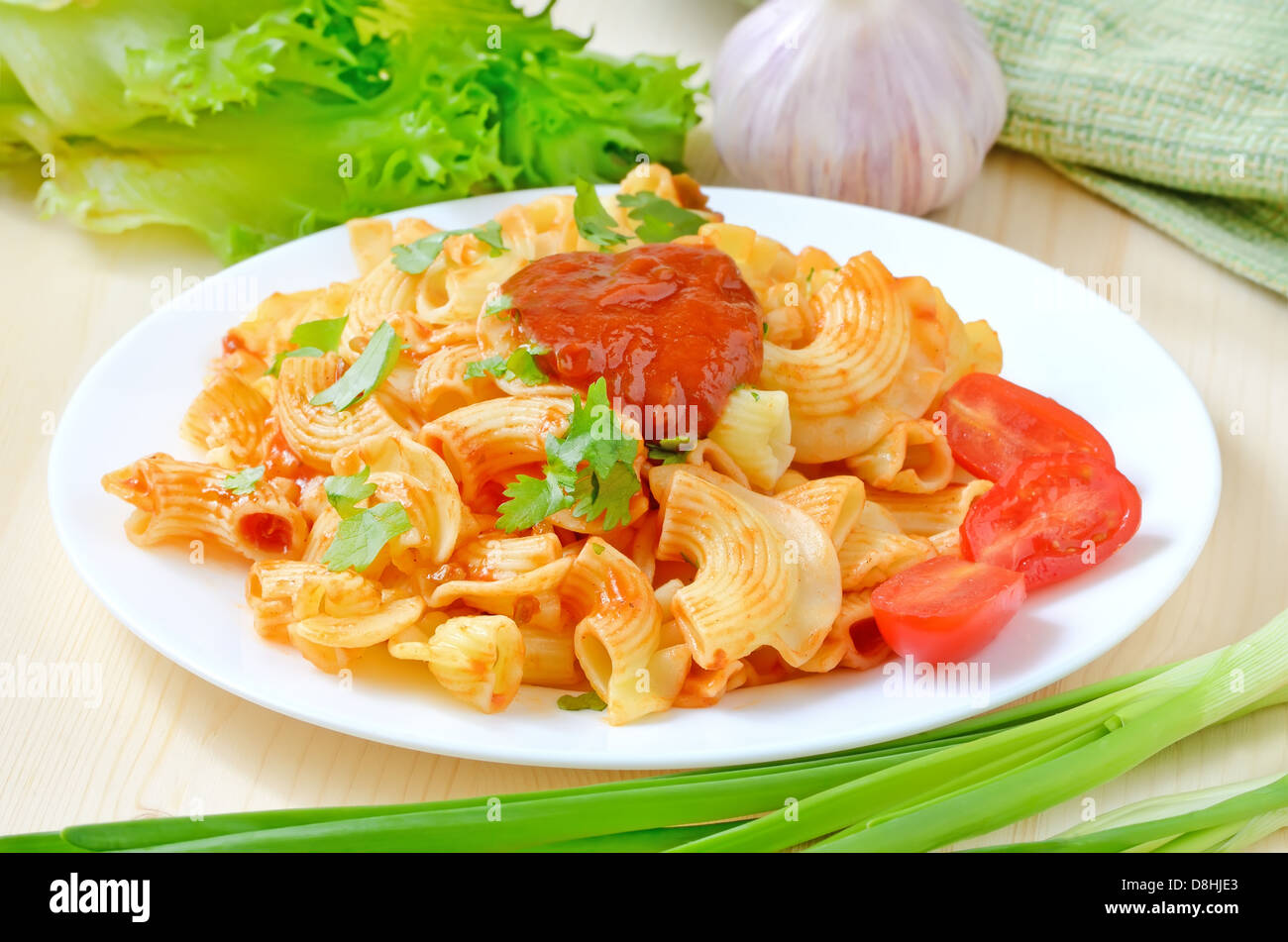 Pasta with ketchup and tomatoes on white plate on the wooden table - Stock Image