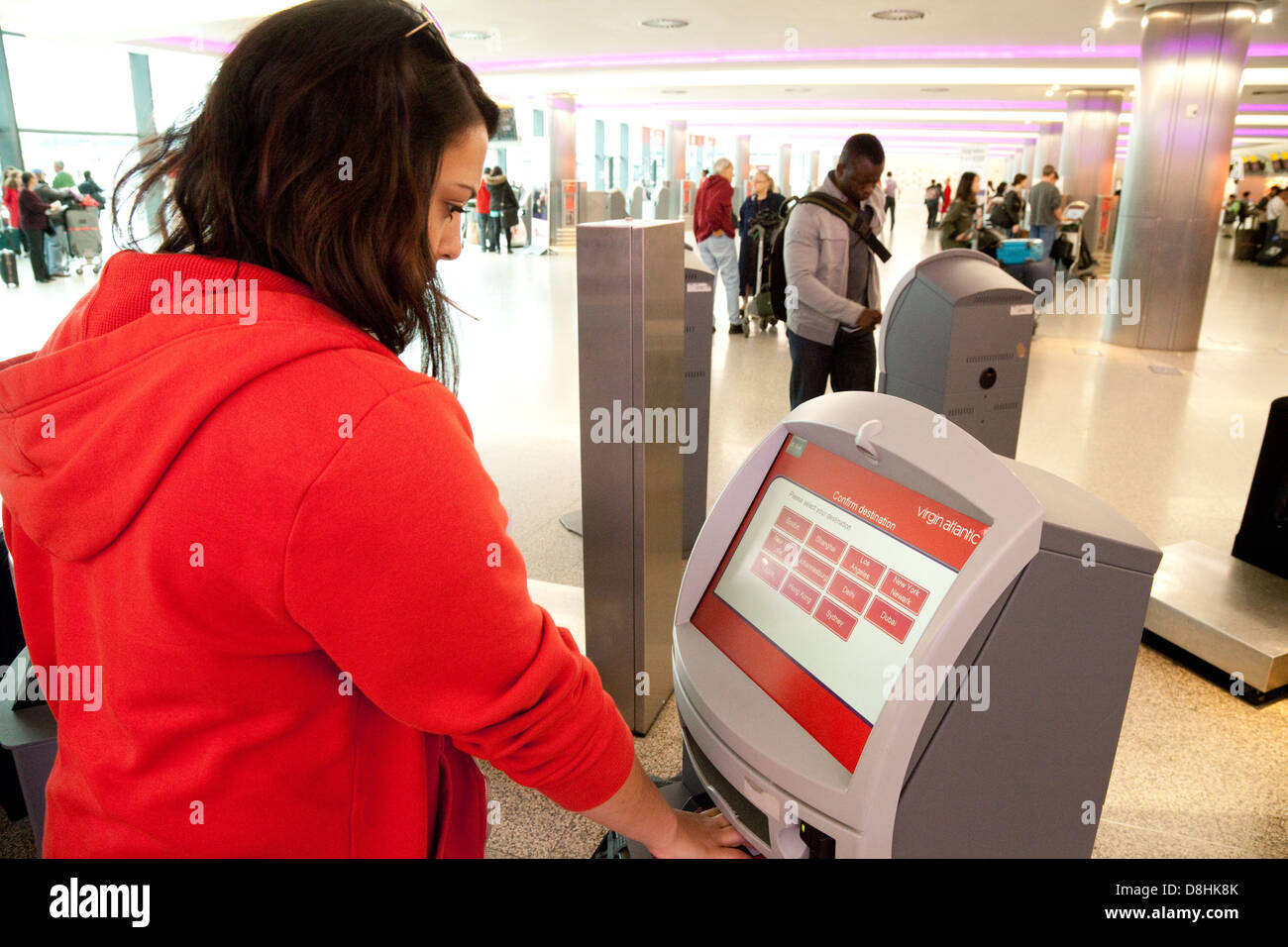 Young woman doing automated check in with Virgin Atlantic