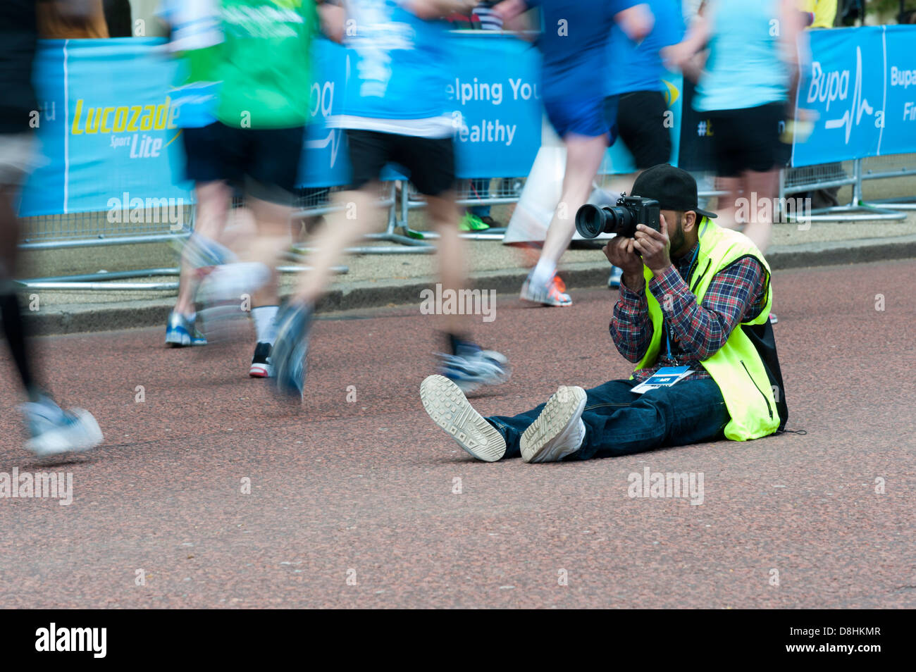 A marathon foto photographer taking photos at the BUPA London 10k run 2013, sitting in road with blurred runners - Stock Image