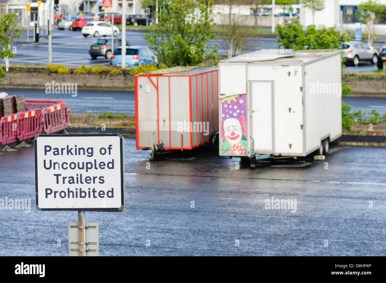 Sign in a car park forbidding parking of uncoupled trailers, with trailers in the background - Stock Image