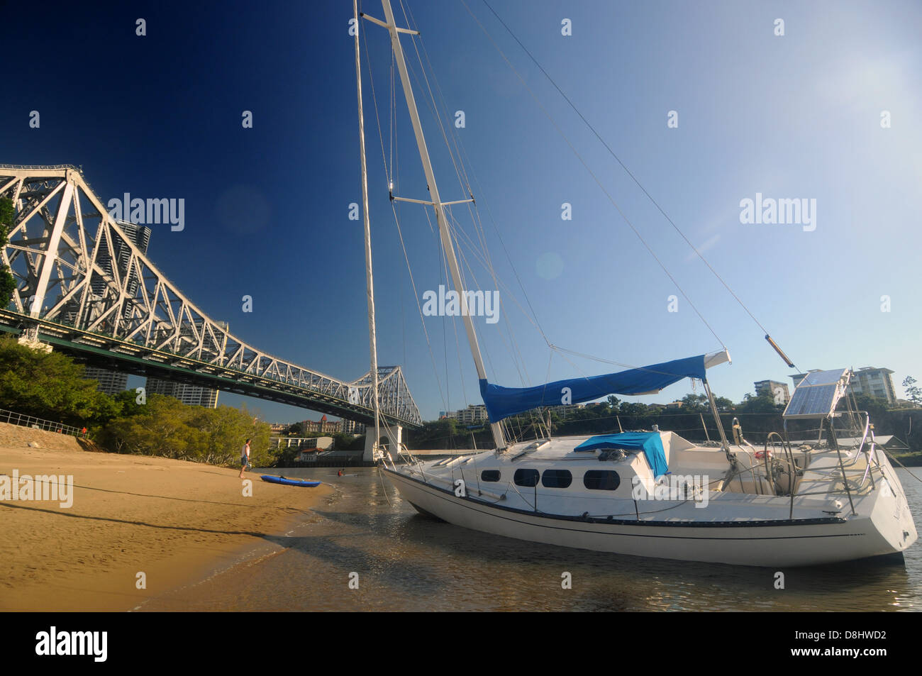 Yacht beached on shores of the Brisbane River, under the Story Bridge, Brisbane, Queensland, Australia. No PR or - Stock Image