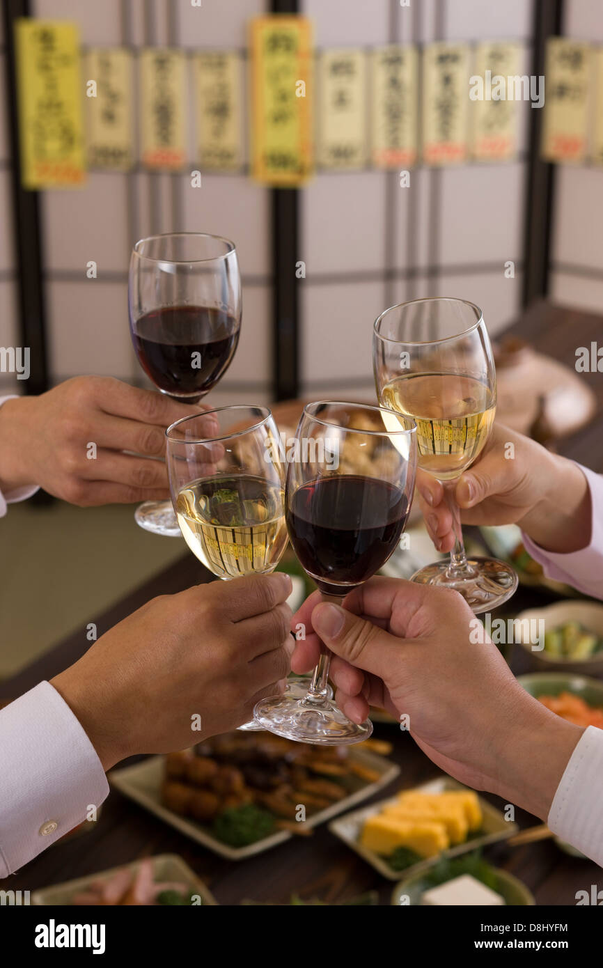 Four People Toasting with Wine at Izakaya Stock Photo