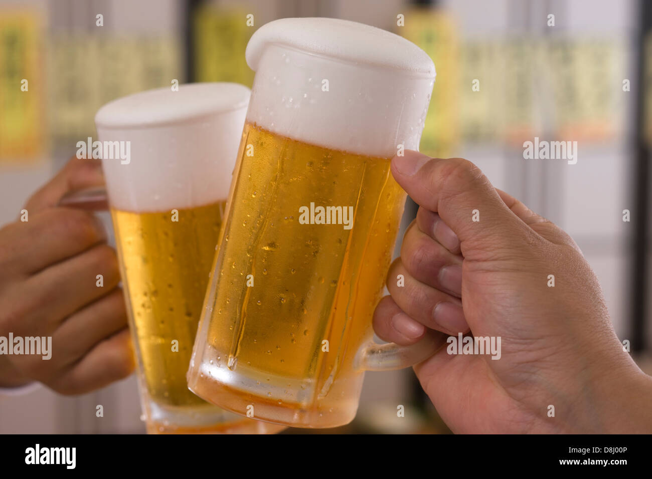 Two People Toasting with Beer at Izakaya Stock Photo
