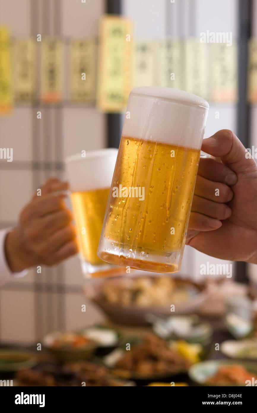 Two People Toasting with Beer at Izakaya Stock Photo