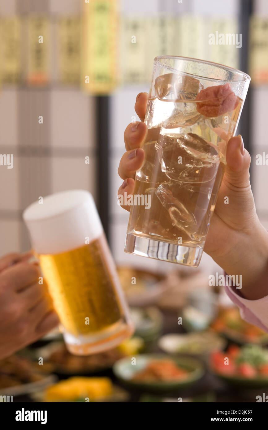 Two People Toasting with Beer and Chu-Hi at Izakaya Stock Photo