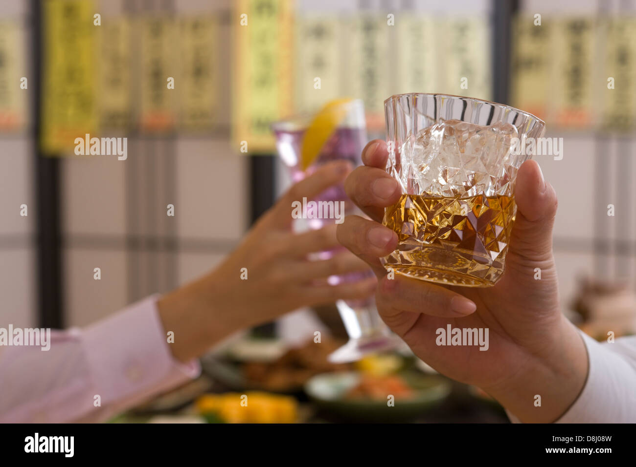 Two People Toasting with Whisky and Cocktail at Izakaya Stock Photo