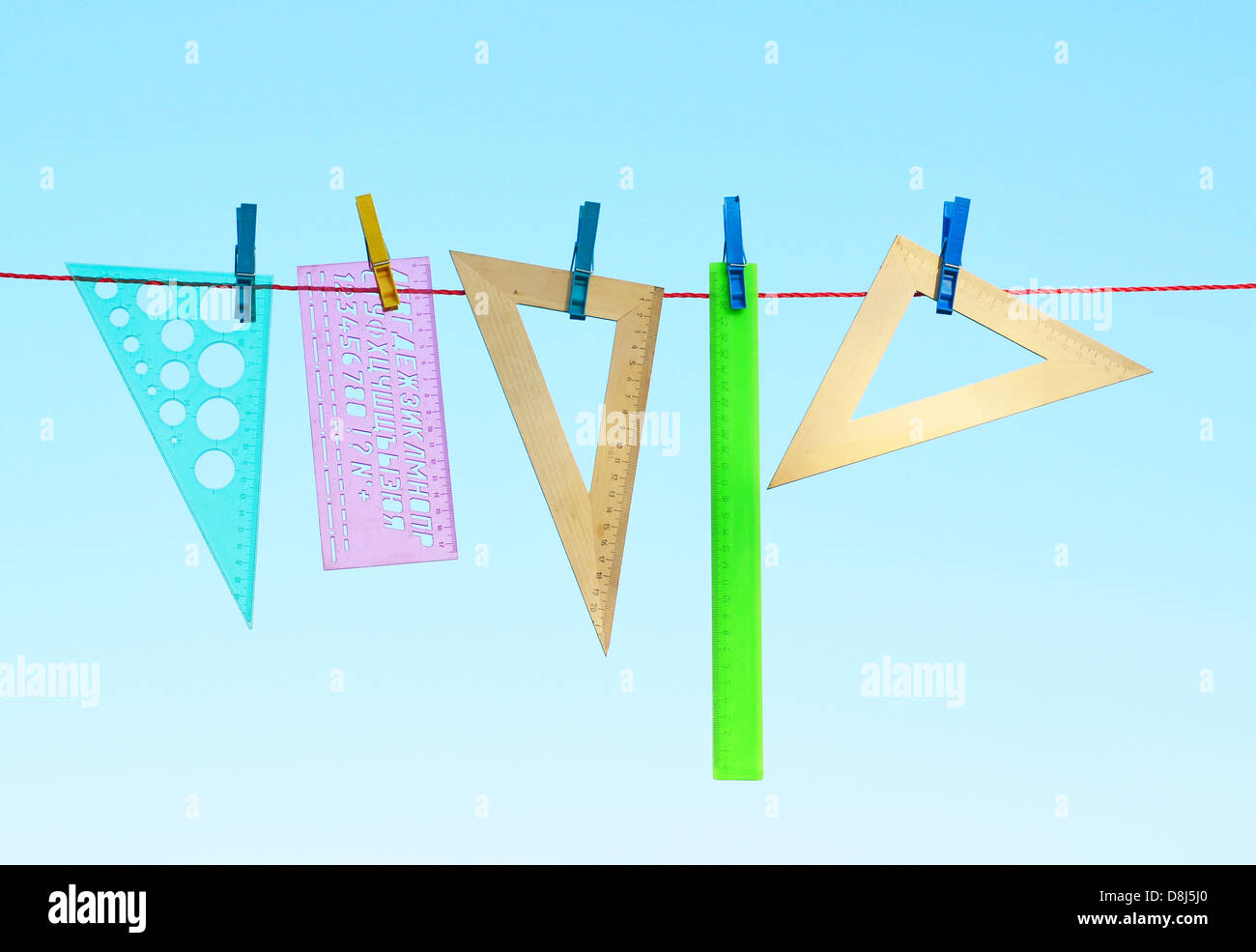 wooden and plastic rulers on washing line against sky Stock Photo