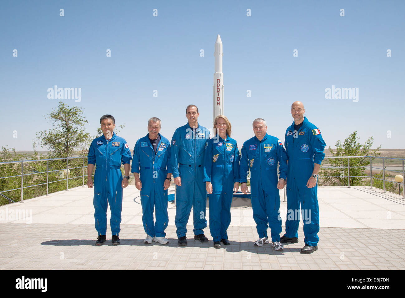 Expedition 36/37 backup and prime crew members pose for pictures in front of a Proton rocket statue May 22, 2013 - Stock Image
