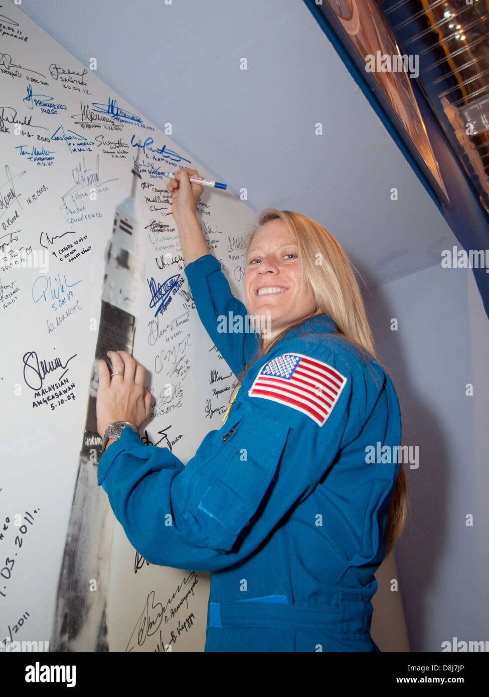 Expedition 36/37 Flight Engineer Karen Nyberg of NASA signs a mural depicting a Soyuz rocket launch in the Korolev - Stock Image