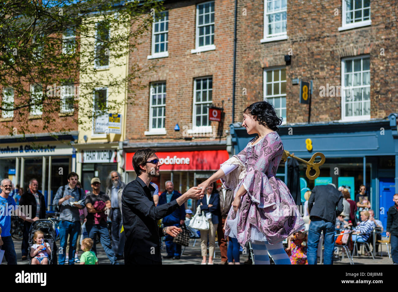 Imitating a clockwork music box dancer, Kate Mior interacts with a young man in her audience during the 2013 York - Stock Image