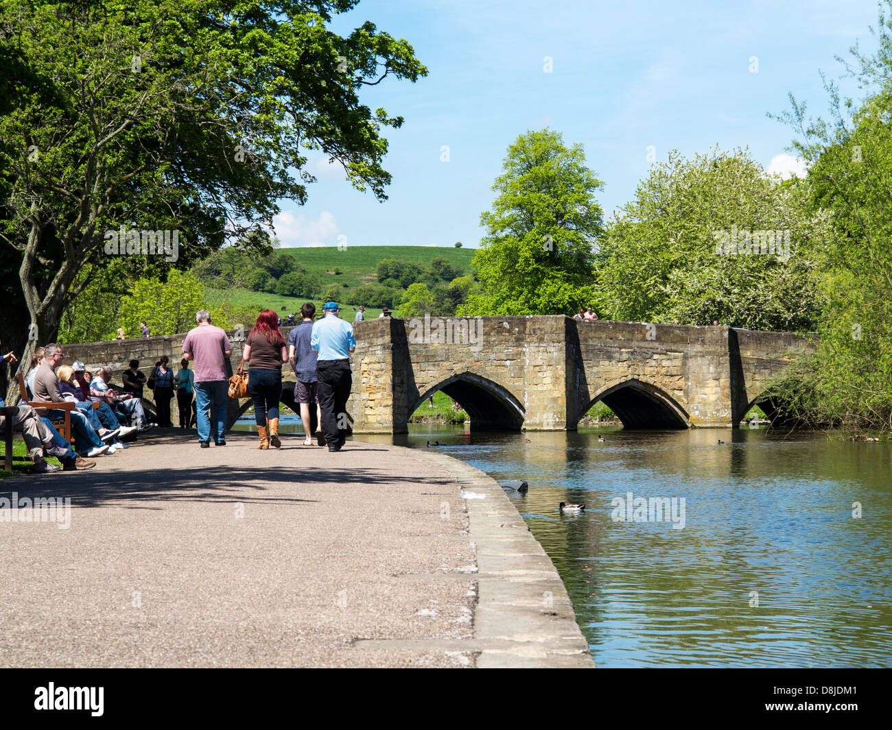 Sitting and walking beside the River Wye in Bakewell, Derbyshire, England. - Stock Image