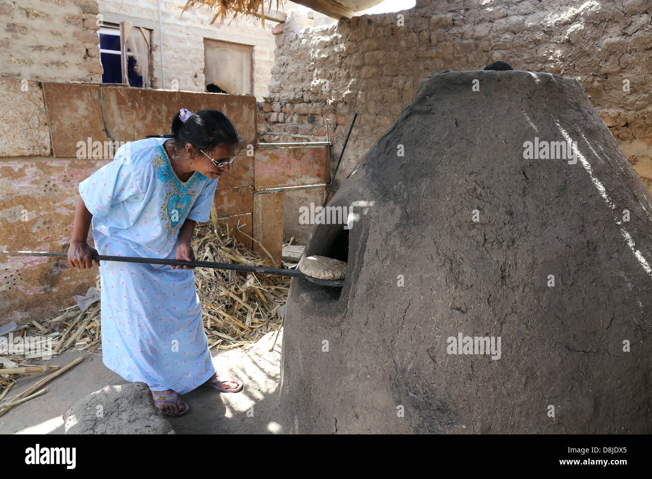 Egyptian woman making flat bread in a stone oven, Upper Egypt - Stock Image