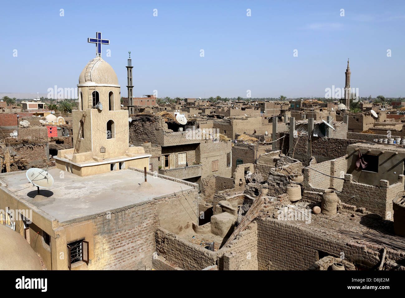 Christian cross on a coptic church and cresent on the minaret of a muslim mosque in Upper Egypt - Stock Image