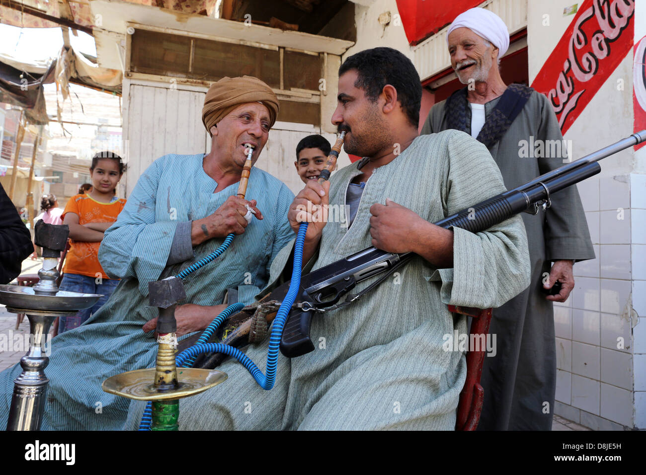 Men withe a rifle smoking Shisha water pipe in a cafe in a village in Upper Egypt - Stock Image
