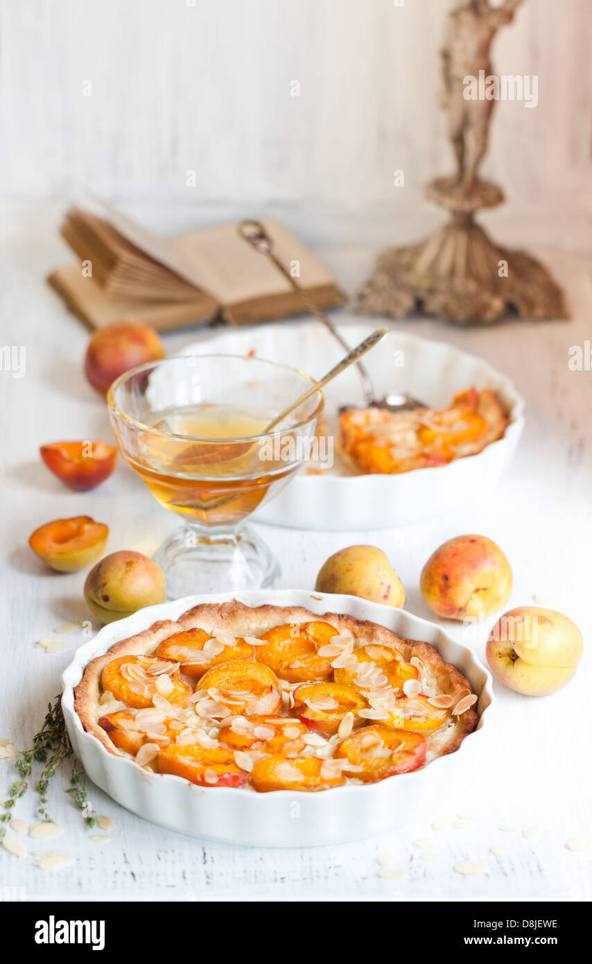 Breakfast with homemade apricot tart with almonds, fresh apricots and honey on white wooden table - Stock Image