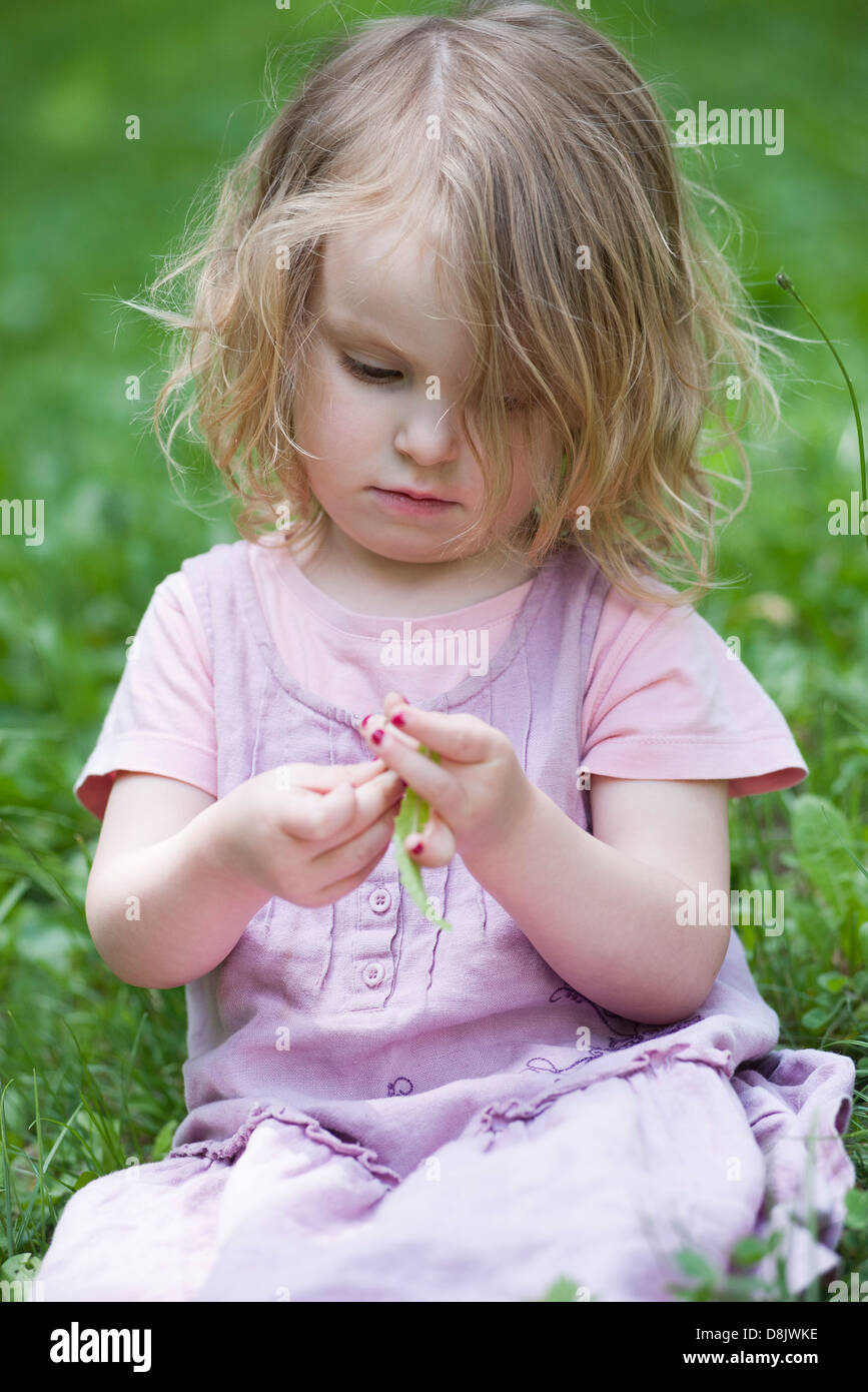 Little girl sitting in grass, playing with blade of grass - Stock Image