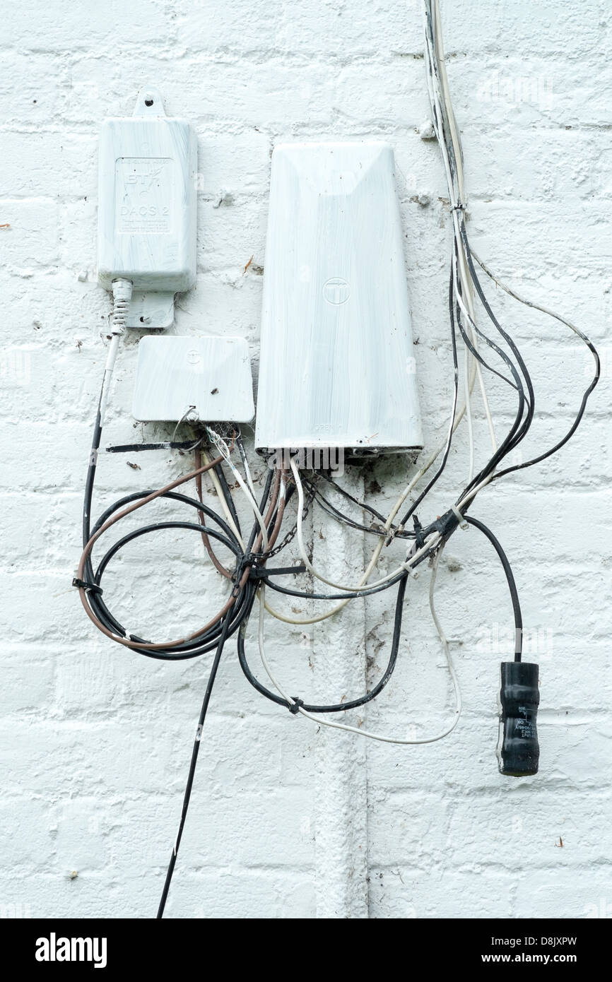 Tangled telephone cables and junction boxes on the wall of a house ...