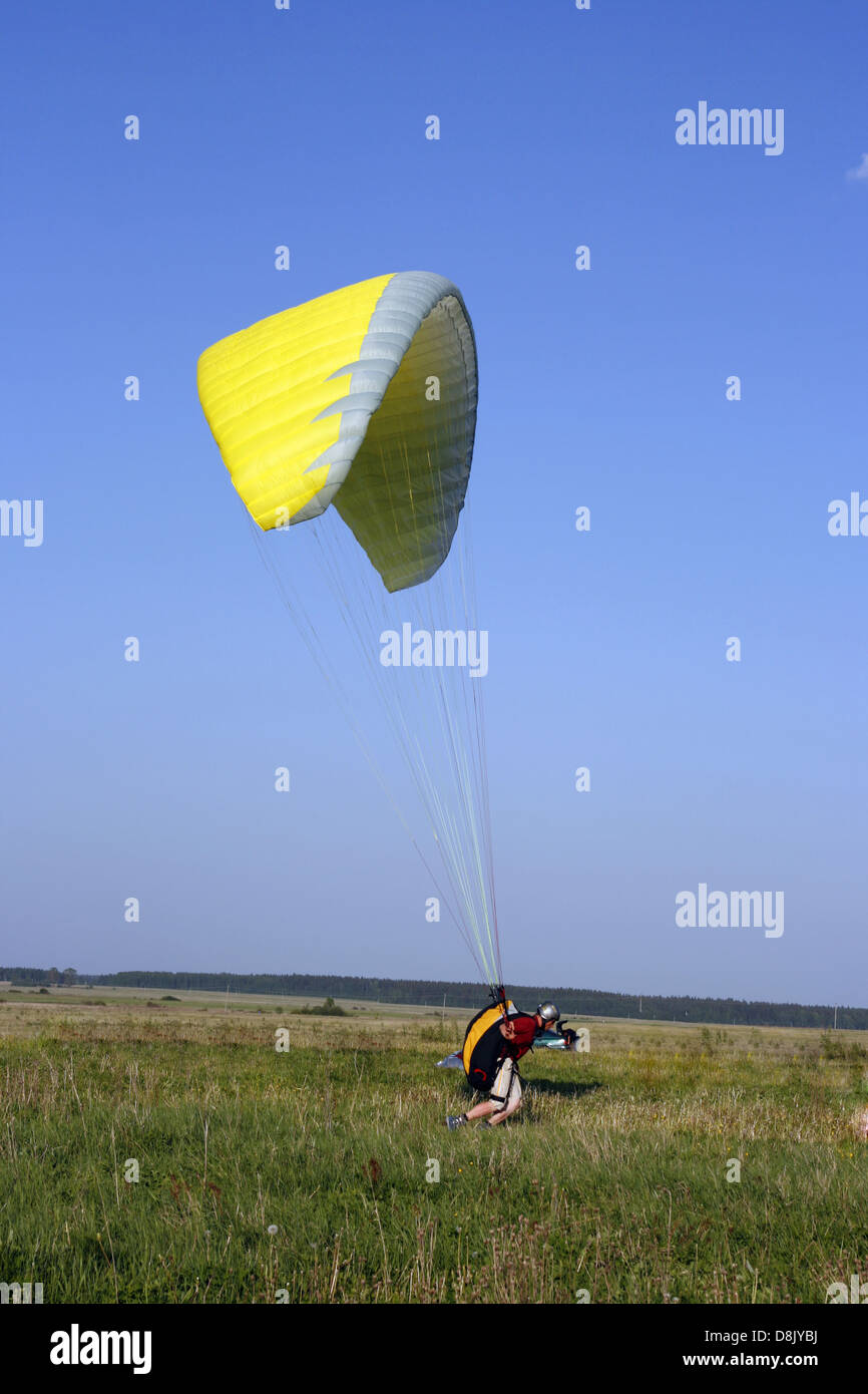 Paraglider landing with yellow wing Stock Photo