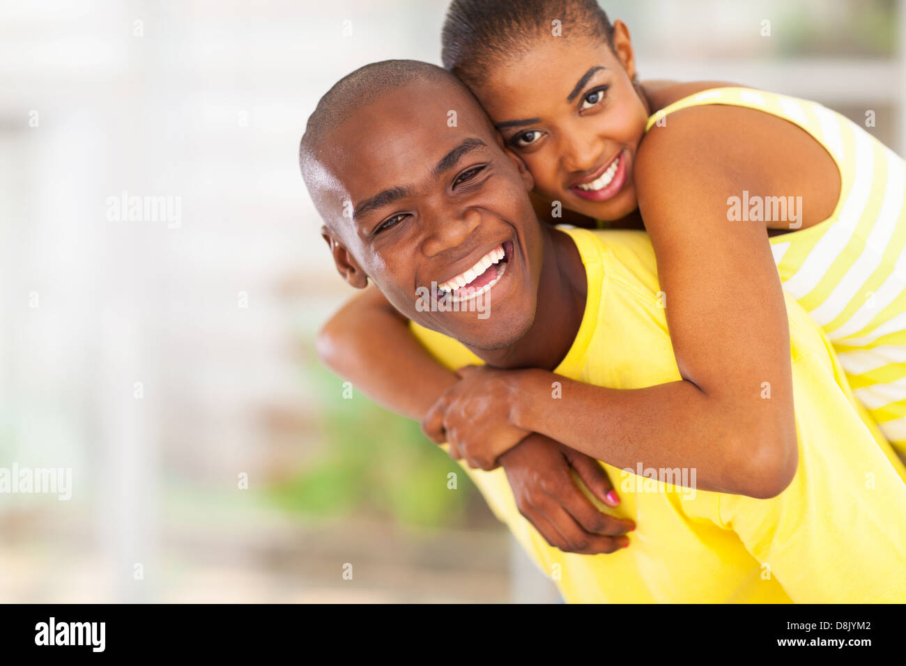 portrait of playful young african couple piggyback - Stock Image