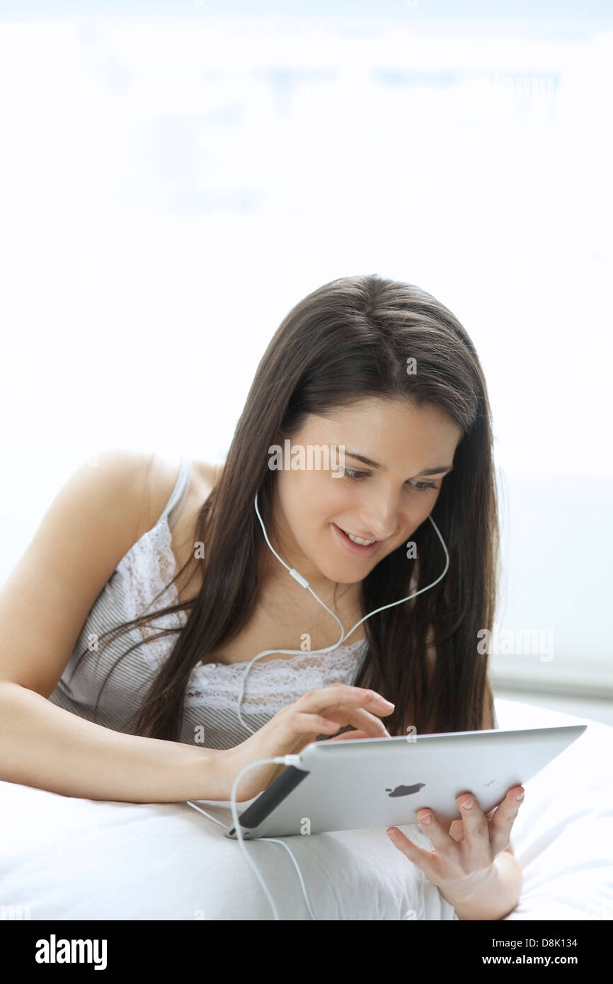 Young woman holding digital tablet while using a headphone in her bedroom - Stock Image