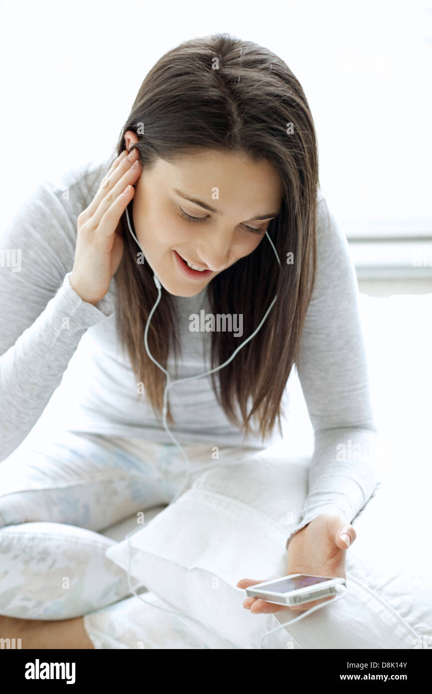 Young Caucasian woman talking on the phone using apple headphones - Stock Image