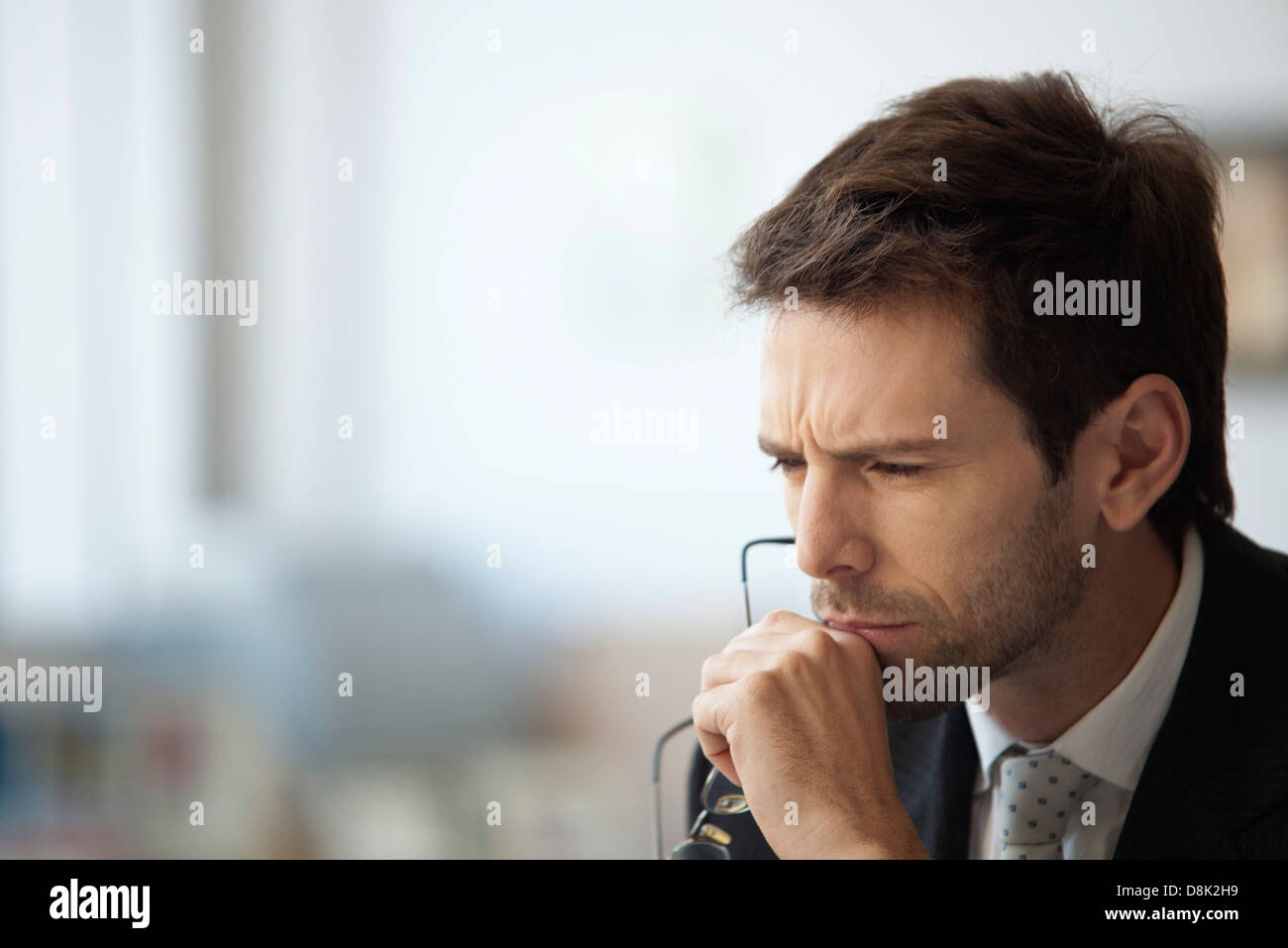 Businessman thinking with furrowed brow - Stock Image