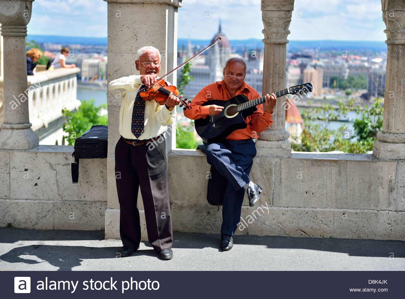 Musicians on Fishermans bastion in Budapest, Danube and parliament in the back - Stock Image