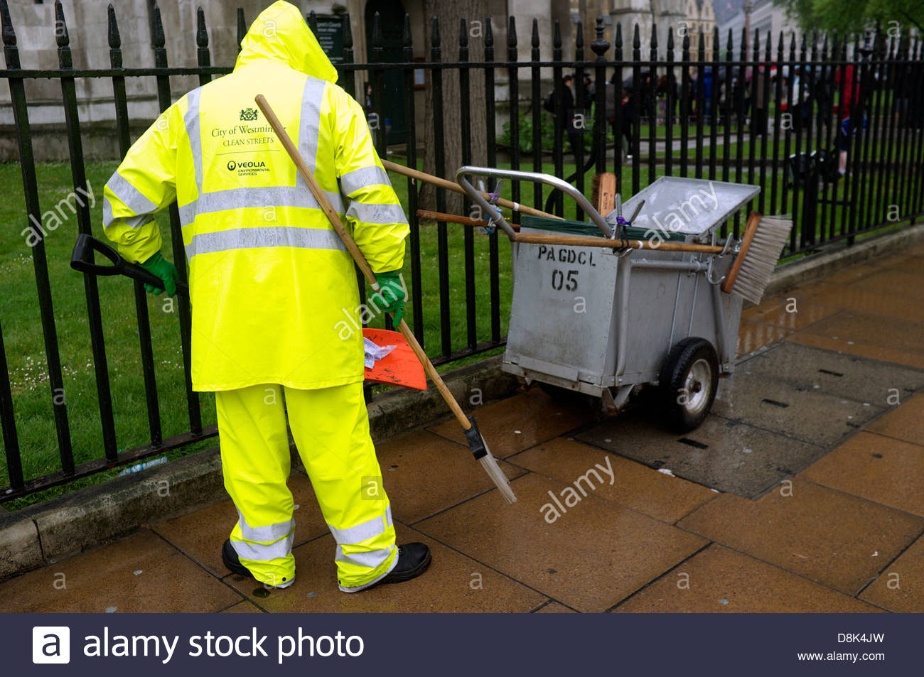 A street cleaner in high visibility waterproof clothing in Wesminster, London, UK. - Stock Image
