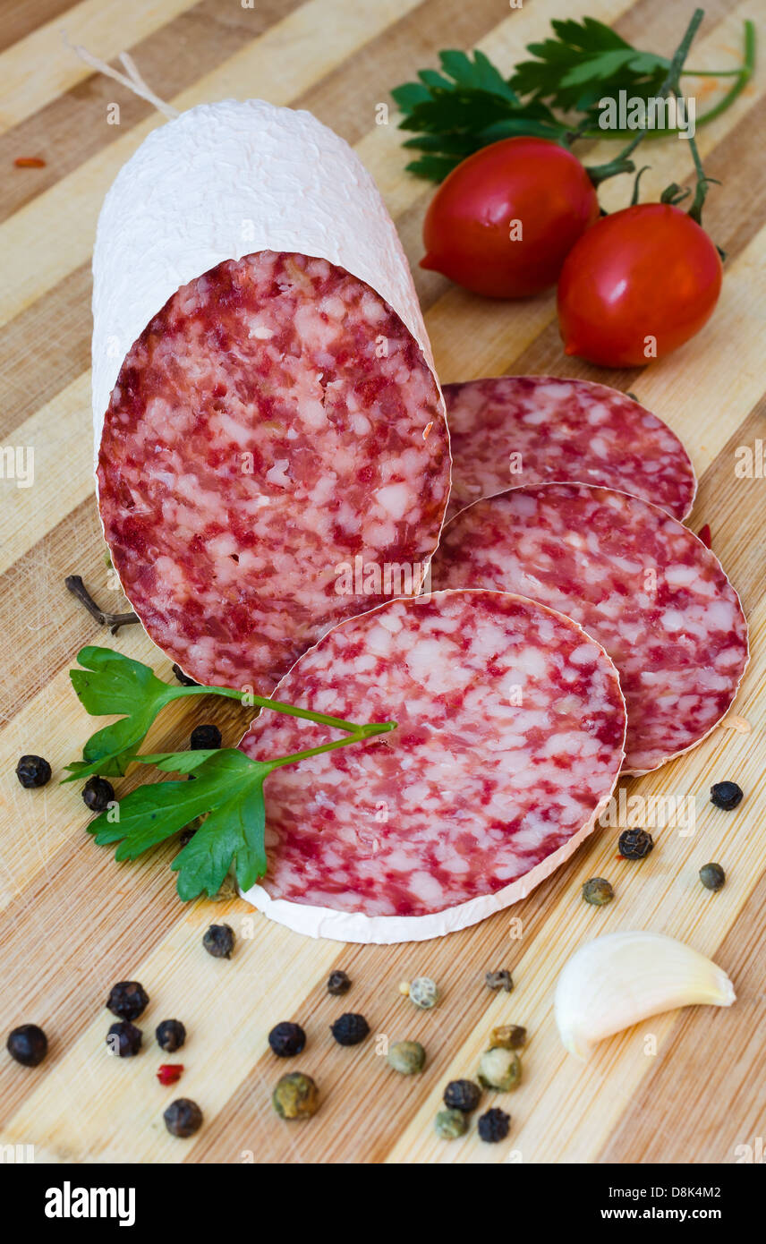 Still life with sliced romanian salami and vegetables - Stock Image
