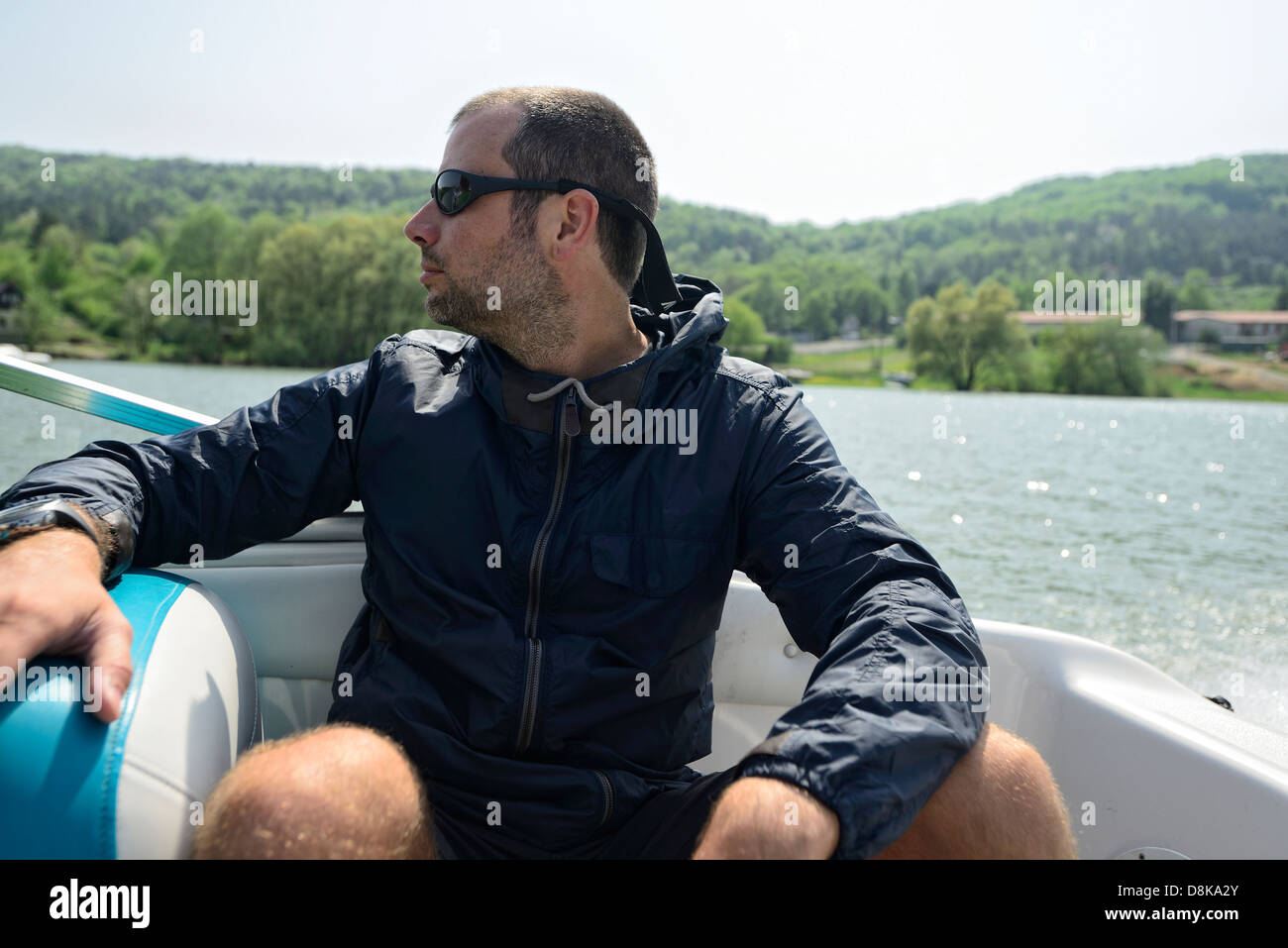 Man in a motorboat speeding away along the shore, looking ahead - Stock Image