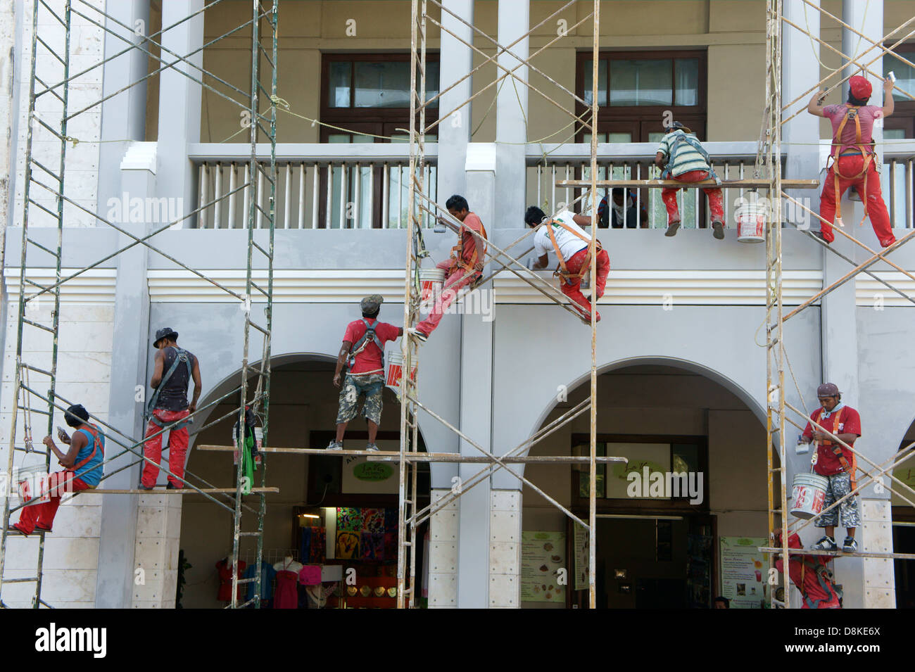 Workers on metal scaffolding painting the facade of a building in Merida, Yucatan, Mexico - Stock Image