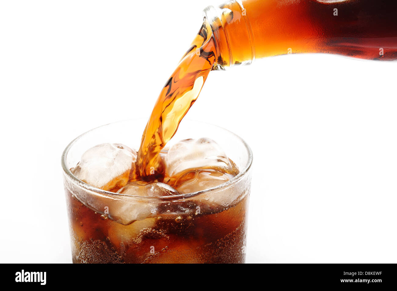 cola pouring into glass on white background - Stock Image