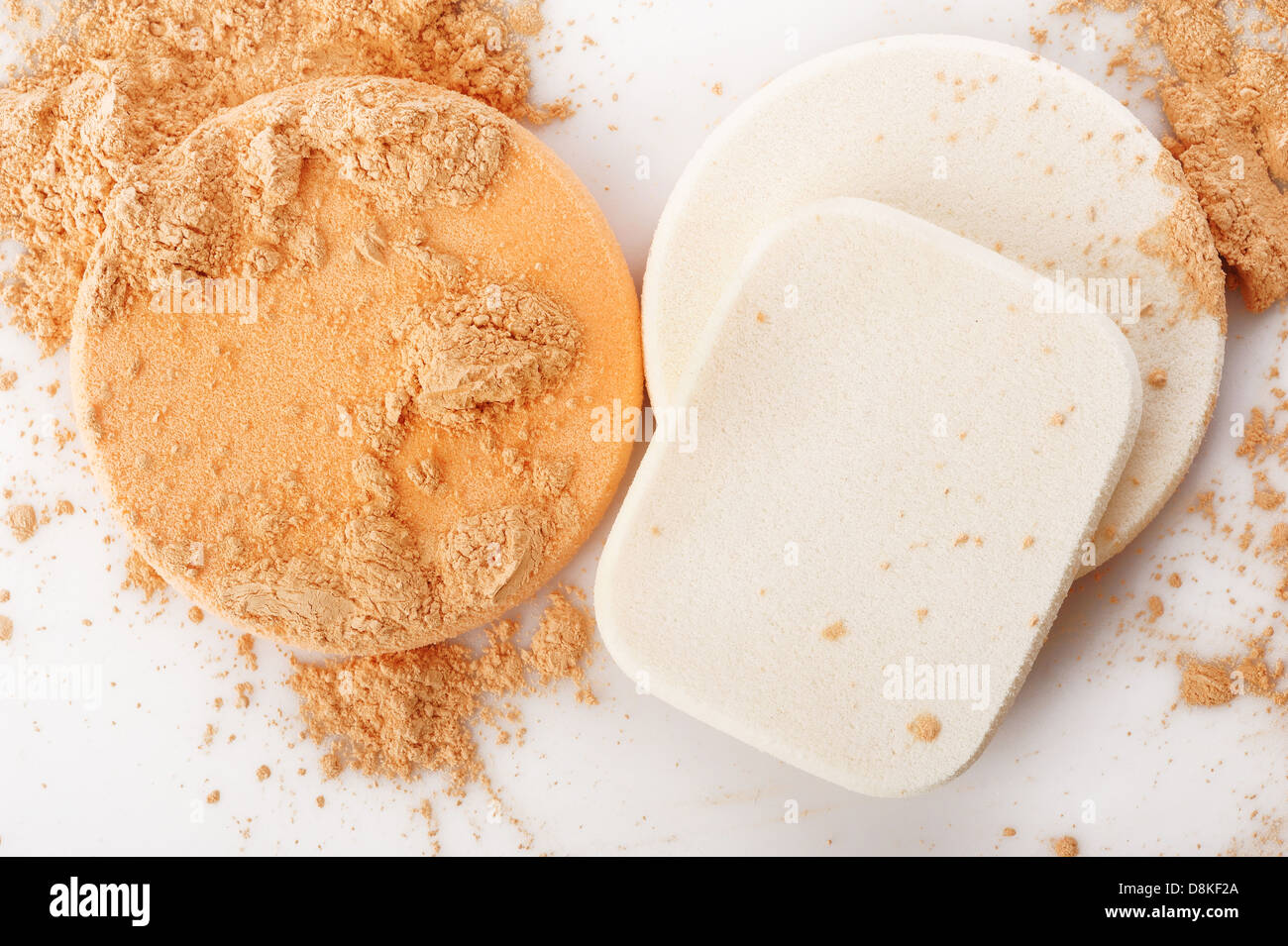 powder and cosmetic sponges on white background - Stock Image