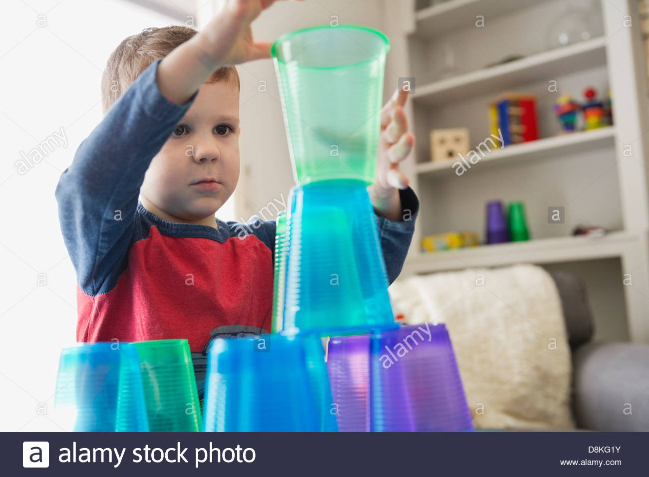 Boy playing with plastic cups at home - Stock Image