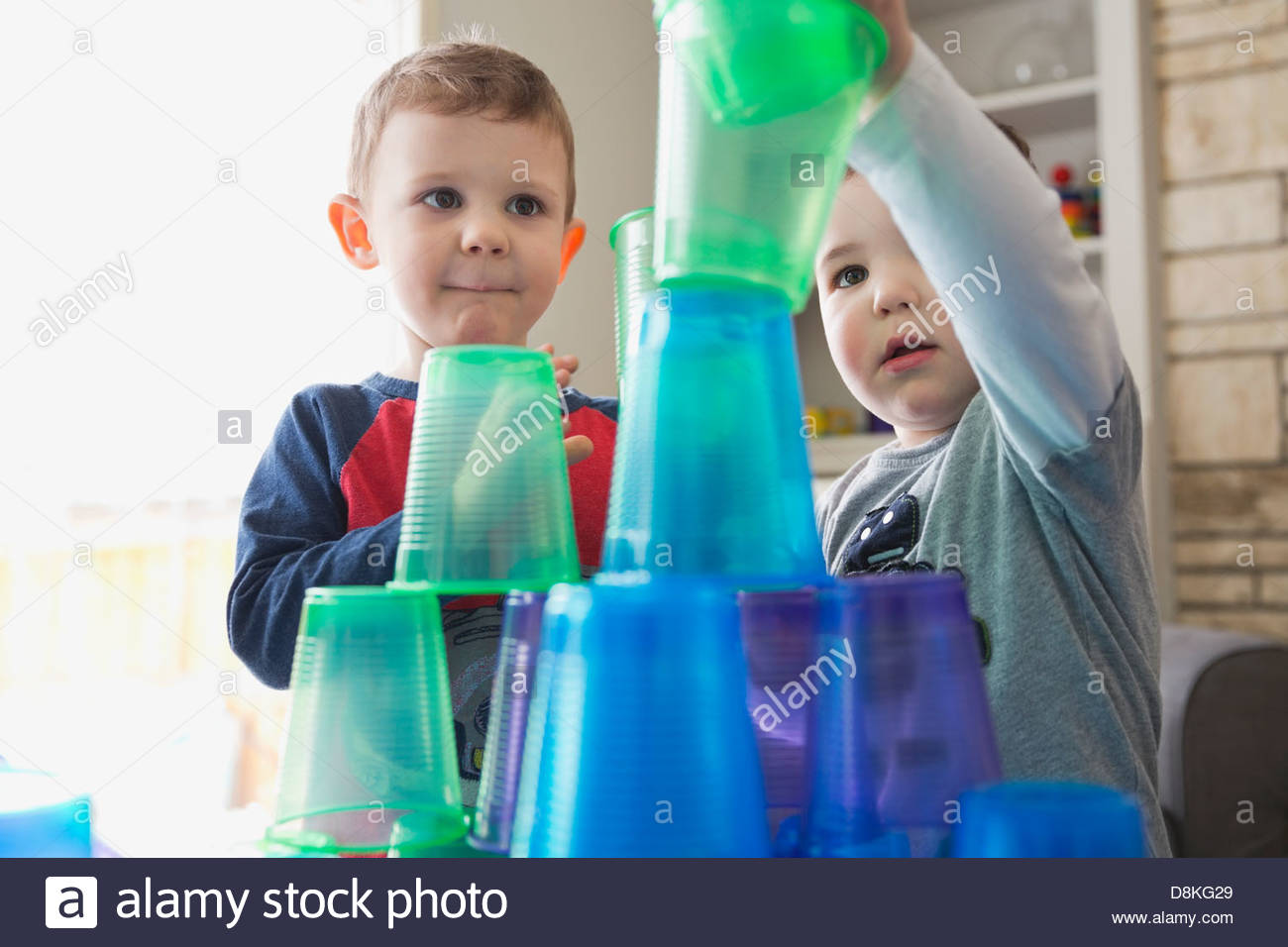 Boys playing with plastic cups at home - Stock Image