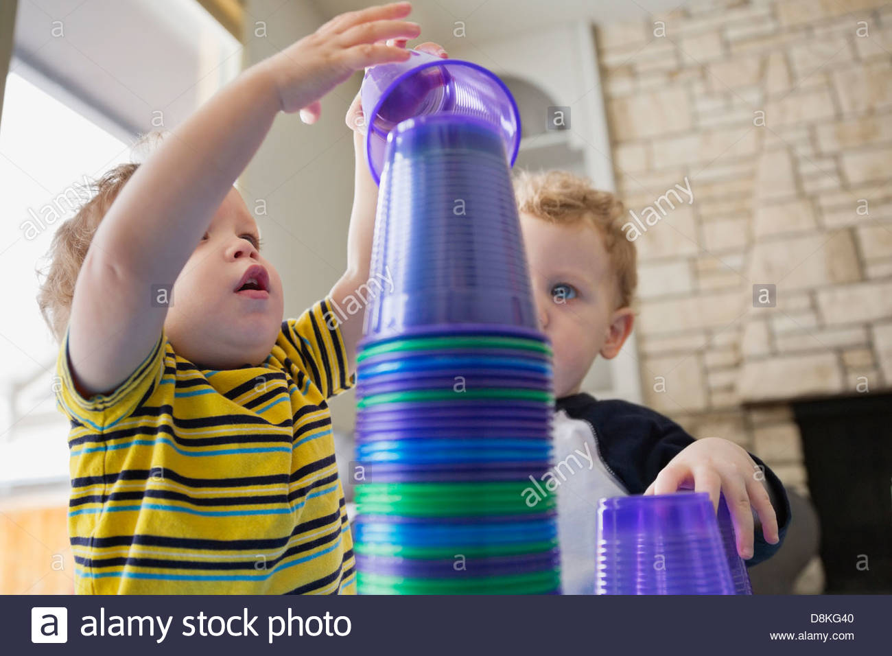 Little boys stacking plastic cups at home - Stock Image