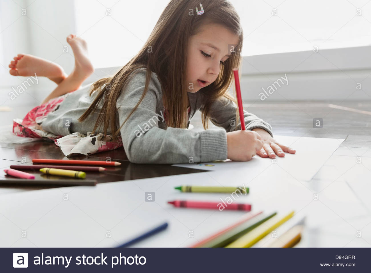 Little girl lying on floor coloring at home - Stock Image