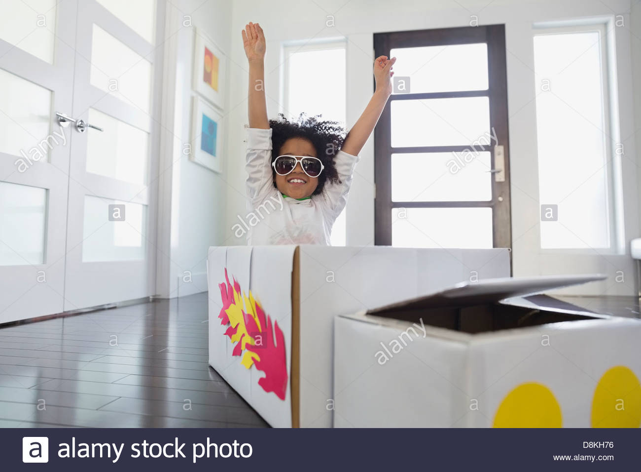 Boy pretending to be race car driver at home - Stock Image