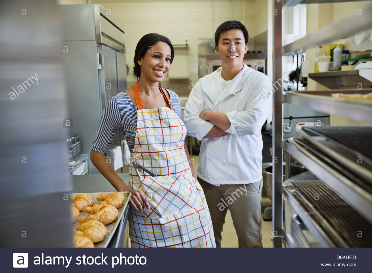 Smiling bakers standing in bakery - Stock Image