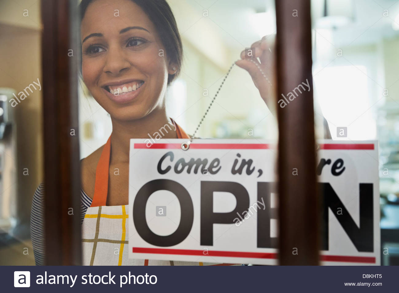 Woman baker hanging 'open' sign on door of bakery - Stock Image