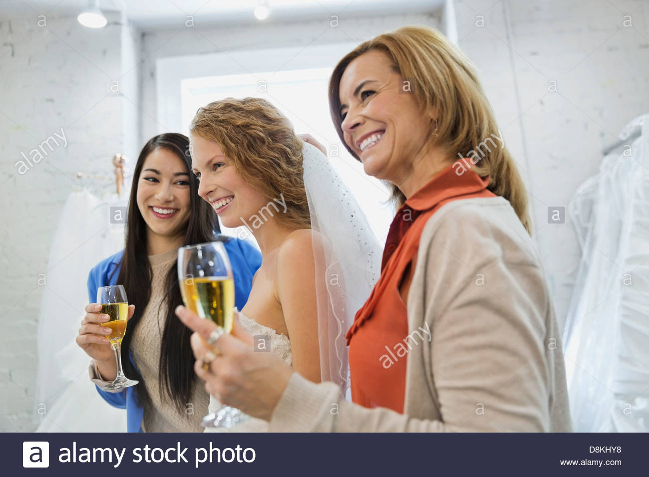 Woman trying on wedding dress with mother and friend at bridal store - Stock Image