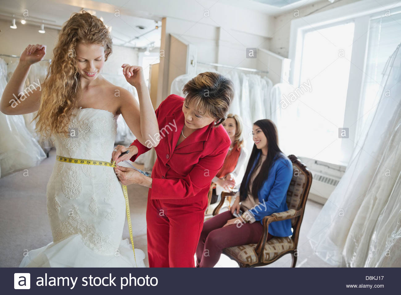 Woman tailor measuring woman in wedding dress at bridal store - Stock Image