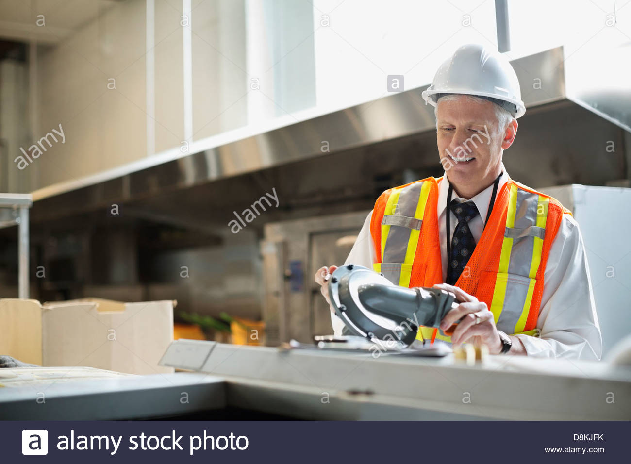 Male architect inspecting kitchen fixture at construction site - Stock Image